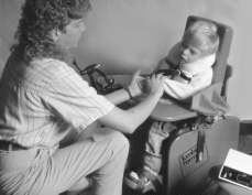 This is a photograph of a woman and a child.  The child is in an assistive sitting device and has straps that hold is feet and chest to the device.  There is a tray in front of him.  The woman is sitting across from the boy and is holding his left hand in both of her hands.
