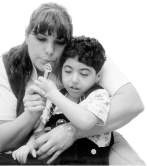 This is a picture of a woman holding a boy on her lap.  The boy has his eyes closed.  The woman is holding a bubble wand with her right hand and a container of bubbles with her left hand.  She is blowing bubbles through the wand and two bubbles float in front of her left hand.  The boy has his left hand on the bubble wand above the woman's right hand.  His right hand is in his lap.