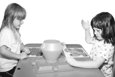 Photo of two girls playing a game.  They are standing across from each other at a table.  On the table between them is the game apparatus.  Behind the game are three large pictures of animals. The girl on the right continues to have her right hand on the game, but has uncovered her eyes.  The girl across the table still watches.