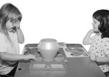 Photo of two girls playing a game.  They are standing across from each other at a table.  On the table between them is the game apparatus.  Behind the game are three large pictures of animals. The girl on the left has her right hand on the game and her left hand over her eyes while the other girl watches.