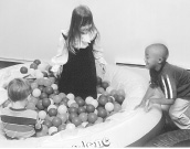 This is a picture of three children and a large container filled with small balls.  One boy sits in the balls with his back to the camera.  A girl is standing in the balls, and another boy is outside of the container of balls, about to come in.