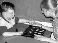 photograph of a woman and boy sitting across the table from one another.  In between them is a board containing symbols.  The boy is handing one of the symbols to the woman.
