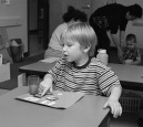 This is a photograph of a boy sitting at a table.  In front of him is a board that contains two objects.  He is pointing to one object on the board.