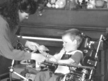 This is a photograph of a boy in a wheelchair and a woman standing in front of him, with one hand on the tray in front of the chair and one hand near the boy's right hand.