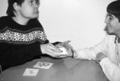 This is a photograph of two people sitting across from each other at a table.  On the table are two cards containing pictures.  The person on the left is placing a third card into the hand of the person on the right.