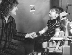 This is a photograph of a boy in a wheelchair and a woman kneeling across from him.  The woman is on the left of the photo and is holding the boy's right hand in her left hand.