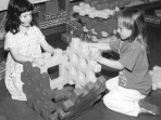 This is a picture of two girls who are sitting on the floor, building a box out of large plastic puzzle-like pieces.  The girls each have two hands on the box they are building.  The girl on the left appears to hold the box steady, while the girl on the right puts pieces into place.