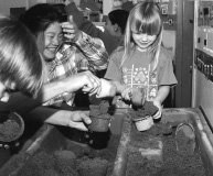 This is a photograph of two girls who are standing at a box filled with sand.  The girl on the right is holding a container and scooping sand into it.  The girl on the left is watching her and laughing.  To the left of the girls another set of hands is also scooping dirt into a cup and a boy's head is leaning over the box.