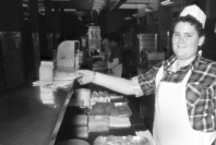 This is a photograph of an adolescent boy standing behind a counter in a cafeteria.  He is wearing a white apron and a hat and is placing a plate of food on the counter beside a carton of milk.  On a lower counter beside him are napkins and food.  He is smiling at the camera.