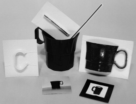 This is a photograph of a mug surrounded by four cards.  The first card contains a raised letter 'C.'  The other three cards contain pictures of mugs that look similar to the actual mug.  Inside the mug is a straw and another card with a straw taped to it.
