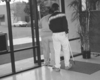 This is a photograph of two people walking out of a door.  They both have their backs to the camera.  The person in the front is opening the door.  The person behind is following the first person and is holding a cane.