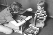 In this picture, a boy and woman are sitting on the floor by a box of large plastic puzzle pieces and a smaller box with other objects.  The woman is leaning toward the boy.  She has something in her closed left hand, and her right hand is facing down, slightly closed.  The boy is looking at her hands.