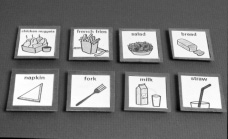 photograph of two rows of cards containing pictures of food and eating utensils and their corresponding labels.