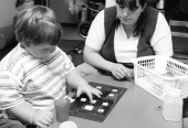 photograph of a woman and a boy seated at a table.  There is a board with small cards containing symbols in front of the boy.  The boy is pointing to a symbol in the center of the board while the woman looks on.