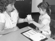 Photograph of a woman and girl sitting at a table.  There is a book containing symbols in front of the girl.  The girl is handing a symbol to the woman.