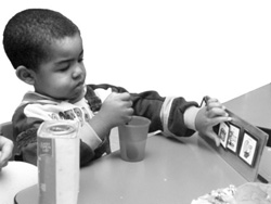 photograph of a boy sitting at a table.  In front of him is a board containing several cards with symbols.  He is using his left hand to manipulate the symbols.  With his right hand he is holding a spoon in a cup of liquid.