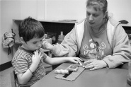 Photograph of a woman and boy sitting at a table.  The woman sits on the side to the boy's left.  On the table in front of the boy is a board with Velcro and three objects.  The boy is manipulating the objects with his left hand and has his right hand near his face.  The woman is using her left hand to hold the board to the table and has her right hand, palm up, gesturing.